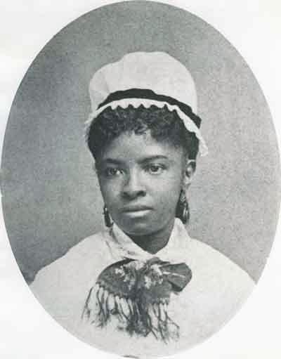 Photographie en noir et blanc de Rebecca Davis Lee Crumpler. Elle porte des boucles d'oreille et un bonnet blanc.