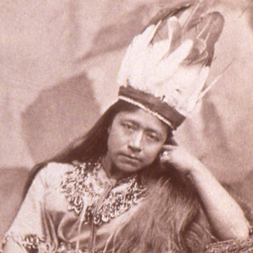 Cette photoghraphie montre Sarah Winnemucca, portant des habits et une coiffe de plumes païutes. Accoudée, elle a le visage appuyé contre sa main gauche et regarde l'objectif.