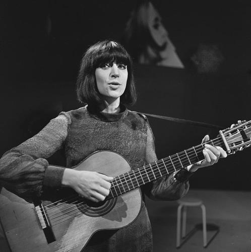 Photographie en noir et blanc d'Anne Sylvestre. Guitare à la main, elle joue et chante.