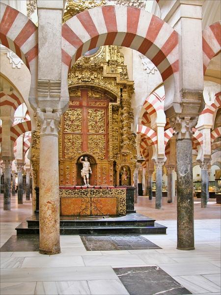 Cette photo représente la Mezquita, la mosquée-cathédrale, de Cordoue. On y voit les colonnades surplombées de pierres rouges et blanches et, au centre de l'image, un autel chrétien.