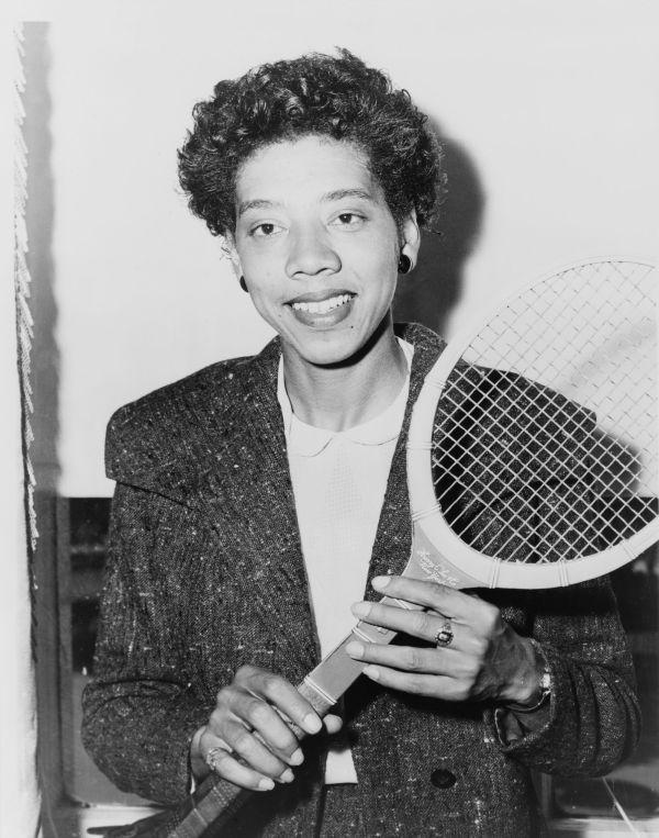 Cette photographie en noir et blanc montre Althea Gibson une raquette de tennis à la main. Elle a les cheveux courts, porte des boucles d'oreille et sourit.