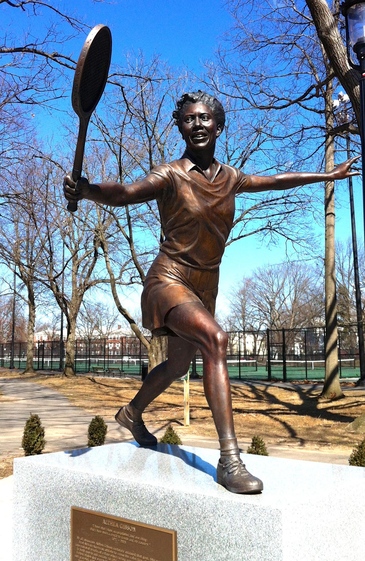 Cette photographie montre une statue d'Althea Gibson. Elle est représentée raquette à la main, en mouvement, bras tendus, en train de jouer au tennis.