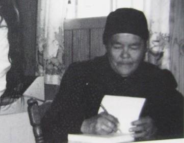 Photographie en noir et blanc d'An Antane Kapesh. Assise à une table, elle porte des habits et un bonnet noir et écrit dans un cahier.