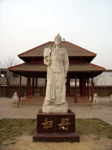 Cette photographie montre une statue de Fu Hao à Yinxu. Fu Hao est représentée debout, en habits militaires, coiffée d'un casque et tenant une hache à la main.