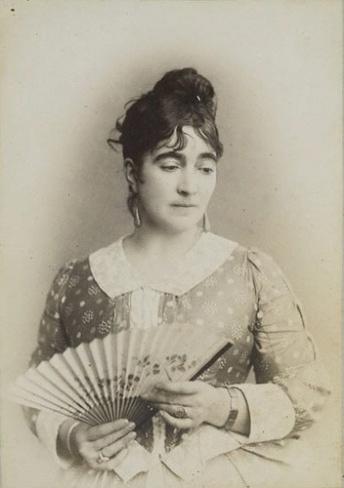 Cette photographie en noir et blanc montre Marie Bracquemond, un éventail à la main. Vêtue d'une robe à motifs géomatriques, avec col et manches blanches, elle a ses cheveux sombres retenus dans un chignon et regarde vers le bas avec un air pensif.