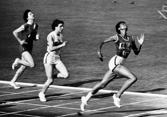 Cette photographie en noir et blanc montre Wilma Rudolph passant la ligne d'arrivée lors des Jeux Olympiques et remportant la médaille d'or. Deux de ses concurrentes sont derrière elle.