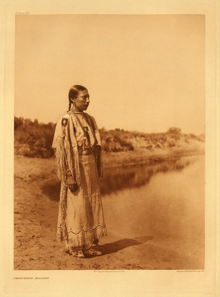 Cette photographie ancienne montre une femme cheyenne debout devant une étendue d'eau et un paysage naturle. Elle porte des vêtements traditionnels et ses cheveux noirs sont retenus en tresse.