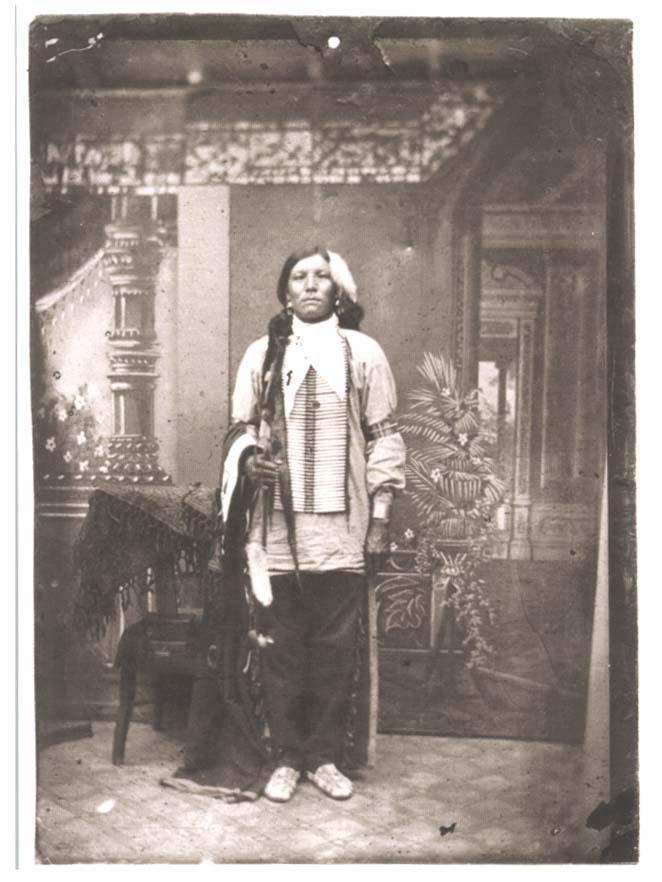 Cette photographie montre un homme amérindien, présumé être le chef Crazy Horse, debout dans un intérieur américain luxueux. Il porte des habits traditionnels.