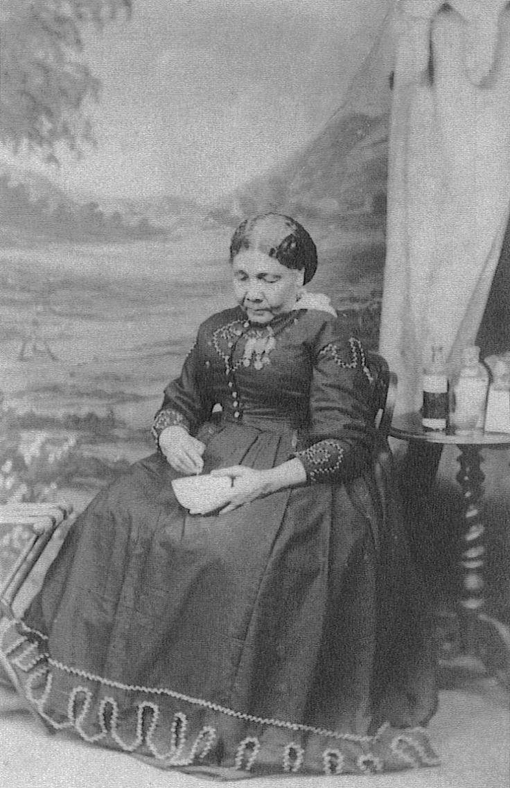 Cette photographie montre Mary Seacole assise sur une chaise. Elle porte une robe longue à la jupe évasée recouvrant jusqu'à ses pieds. Ses mains reposent sur ses cuisses, sa main droite tient un bol. Cheveux soigneusement coiffés, elle regarde vers le bas. Derrière elle, on aperçoit un guéridon avec plusieurs flacons.