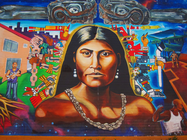 Cette photographie montre une fresque murale représentant Toypurina. Elle a les cheveux lâchés et porte des boucles d'oreille et un collier de coquillages.