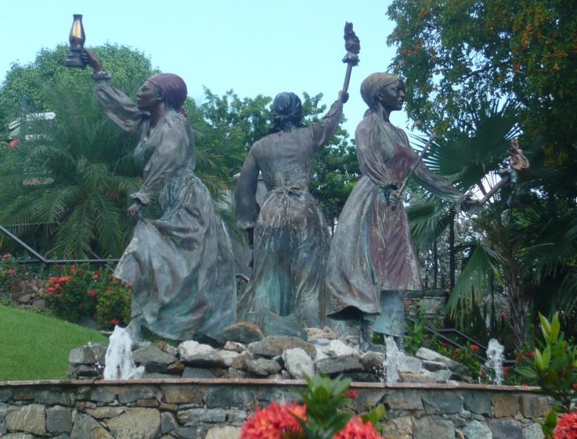 Cette photographie montre une statue de trois femmes, Queen Mary, Queen Agnes et Queen Mathilda. L'une tient une lampe, une autre tient une torche allumée et la troisième tient une machette.