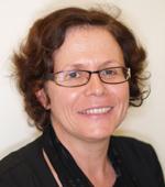 Cette image est une photographie d'Anne-Marie Lagrange. Elle porte une veste noire et des lunettes. Ses cheveux chatains sont coupés courts ; elle sourit.
