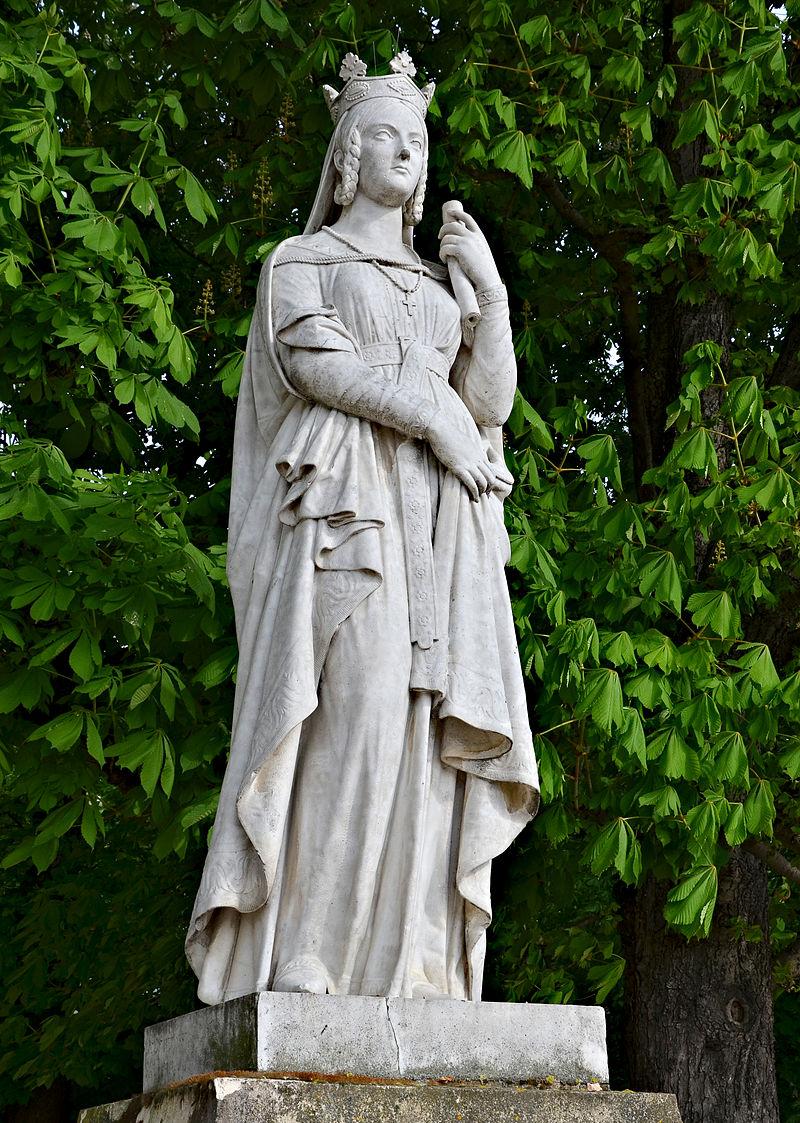 Cette photo montre une statue en pied de Sainte Bathilde. Elle porte une robe longue, une couronne royale, un manteau fin, et tient un rouleau à la main. Réalisée par Victor Thérasse, la statue se trouve au jardin du Luxembourg à Paris.