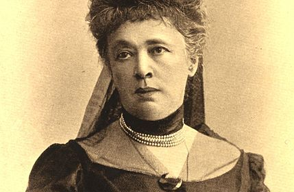 Cette image est un portrait de Bertha von Suttner. Elle porte une riche robe d'époque en tissu sombre, un collier de perles à plusieurs rangs et une coiffure sophistiquée.