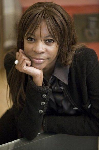 Cette image est une photographie de Dambisa Moyo. L'économiste et autrice est accoudée, le menton reposant dans sa main droite. Elle porte une chemise et une veste noire. Elle sourit.