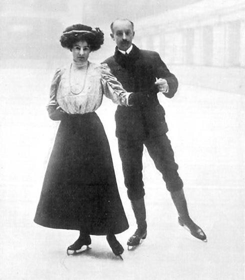 Cette photographie en noir et blanc montre Edgar et Madge Syers aux Jeux olympiques de 1908. Madge, à gauche, porte une jupe sombre comme ses patins et un haut clair. Edgar, à droite, tient Madge par la taille et par la main. Il porte un pantalon et une veste sombres.