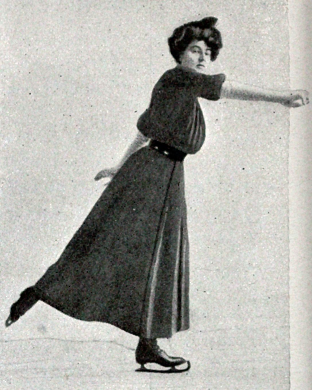 Cette image en noir et blanc montre Madge Syers en train de patiner. Vêtue d'une robe, d'une ceinture et de patins sombres, elle est inclinée vers l'avant. Bras droit tendu en avant, elle lève le pied droit en arrière.