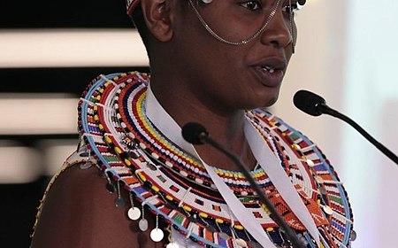 Cette photographie montre Nice Nailantei Leng'ete en habits maasaïs. Elle porte une tunique blanche brodée de perles colorées, un collier rond traditionnel en rangs de perles et une coiffe de perles. Elle se tient devant des micros, visiblement en train d'intervenir en public.
