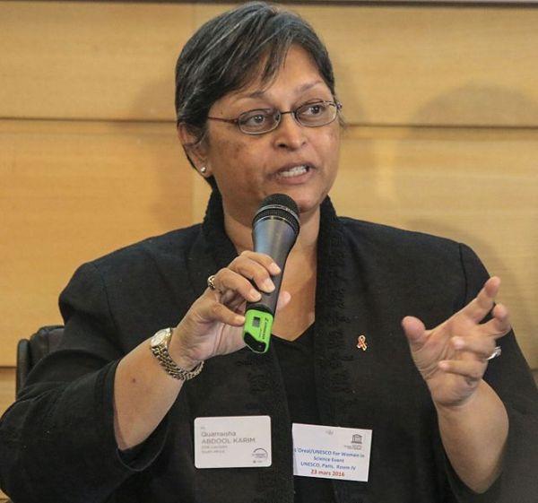 Cette photographie montre Quarraisha Abdool Karim, un micro dans sa main gauche et sa main droite ouverte. Bouche entrouverte, elle est en train d'intervenir lors de la remise des prix L'Oréal-Unesco. Elle a les cheveux courts et grisonnants, porte des lunettes, une veste noire et un montre bracelet.
