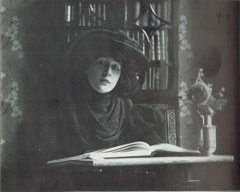 Cette photographie en noir et blanc montre Rosemonde Gerard assise devant une bibliothèque, un gros livre ouvert devant elle. Elle porte une robe noire et un chapeau noir. A côté d'elle sur la table se trouve un bouquet dans un vase.