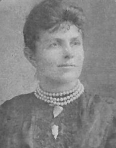 Cette photographie en noir et blanc montre une femme de profil, portant une veste sombre et un collier ras-du-cou à trois rangs de perles blanches. Il pourrait s'agir de Maria Beasley