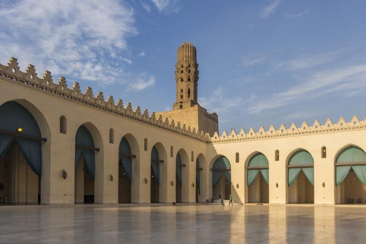 Cette photographie montre la cour de la Mosquée Al-Hakim au Caire, sous un ciel bleu avec quelques nuages de beau temps.