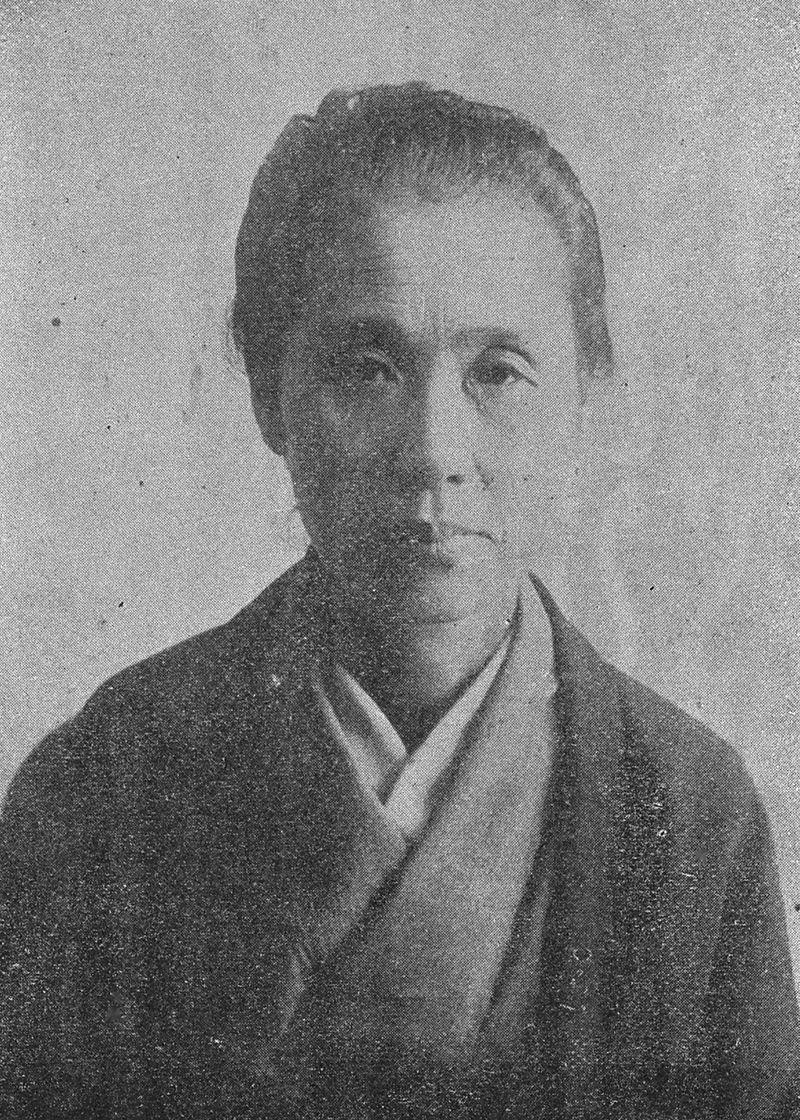 Cette image est une photographie en noir et blanc d'Ogino Ginko. Elle regarde la caméra avec un air sérieux.