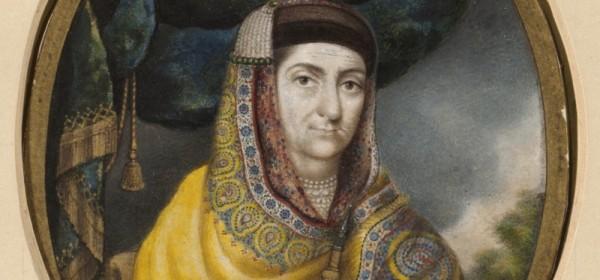 Cette image représente la Bégum Samru en habits moghols. Elle porte un manteau brodé de riches motifs et un voile sur ses cheveux, retenu par des rangs de perle. Elle tient un sabre à la main.