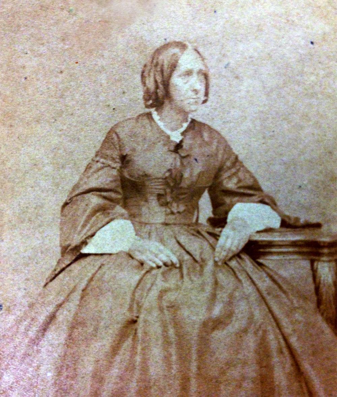 Cete photo ancienne et abimée montre Sarah Harris Fayerweather en robe d'époque sombre, assise sur une chaise et accoudée sur un guéridon.