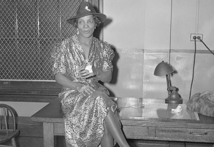 """Cette photographie en noir et blanc montre Stephanie St. Clair, assise sur une table, les jambes croisées. Elle porte une robe aux manches mi-courtes et s""""arrêtant sous les genoux, et un chapeau."""