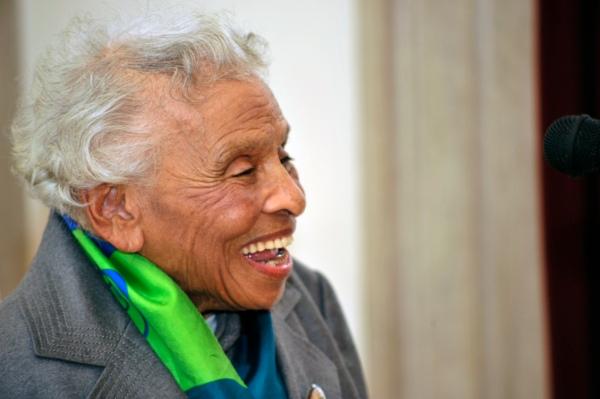 Cette photographie montre Olivia Hooker à l'âge de 97 ans. Ses cheveux blancs sont courts. Elle porte une veste grise et un foulard vert et bleu. Regardant vers la droite, elle a un large sourire.