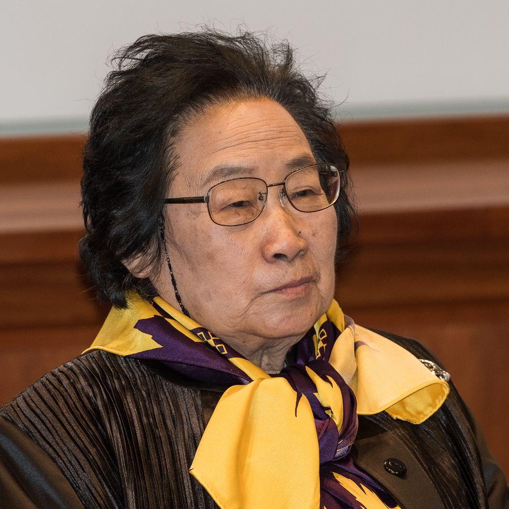 Cette photographie montre Tu Youyou à Stockholm en 2015 lors de la remise de son prix Nobel. Elle porte un foulard jaune et violet, une veste noire et des lunettes.