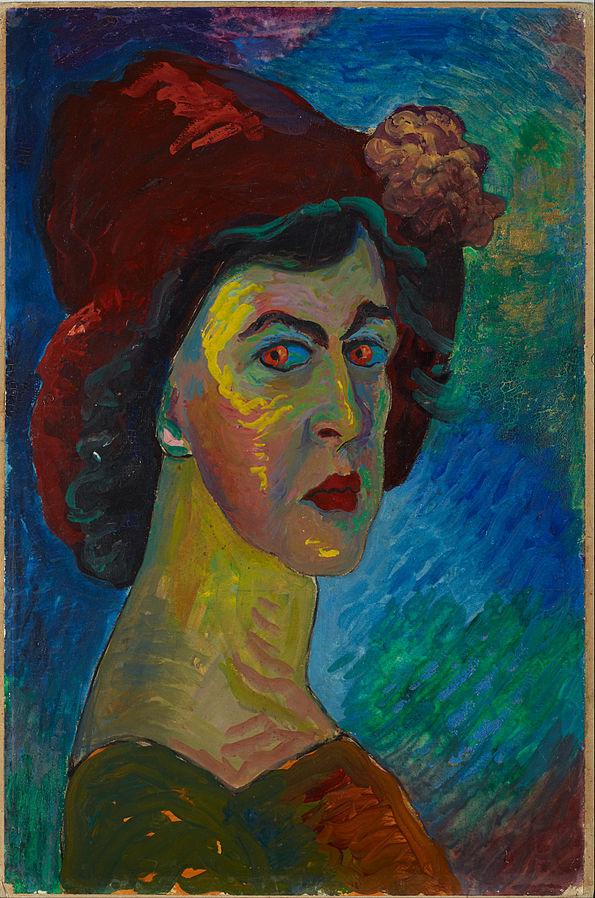 Cette image est un autoportrait de Marianne von Werefkin ; elle est représentée de profil, regardant vers le spectateur. Le tableau est dans des tons bleus, verts et rouges. Elle porte un chapeau rouge avec une fleur, et ce rouge est rappelé dans ses yeux, ses lèvres et sa robe.
