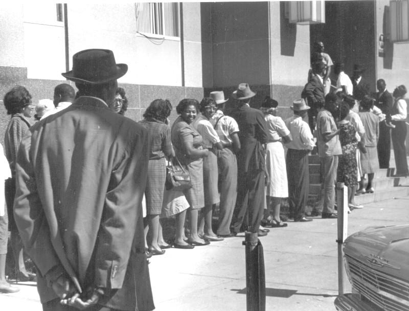 Cette photographie en noir et blanc montre des citoyens noirs faisant la queue devant le palais de justice de Dallas pour s'inscrire sur les listes électorales, en 1963. On voit une douzaine de femmes et d'hommes debout, en file le long d'un bâtiment clair.