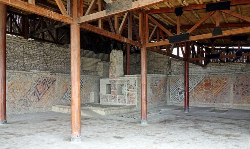 Cette photographie montre une salle funéraire de la huaca Cao Viejo, dans le site archéologique El Brujo au Pérou.  Les murs anciens sont couverts de fresques géométriques colorées. Un plafond de bois récent a été créé, supporté par des poutres de bois.