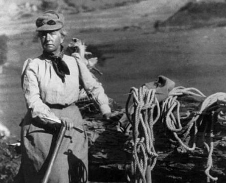 Photographie en noir et blanc montrant Fanny Bullock Workman lors d'une de ses expéditions. Assise devant un paysage montagneux, elle porte une jupe longue. Du matériel d'alpinisme est disposé à côté d'elle.