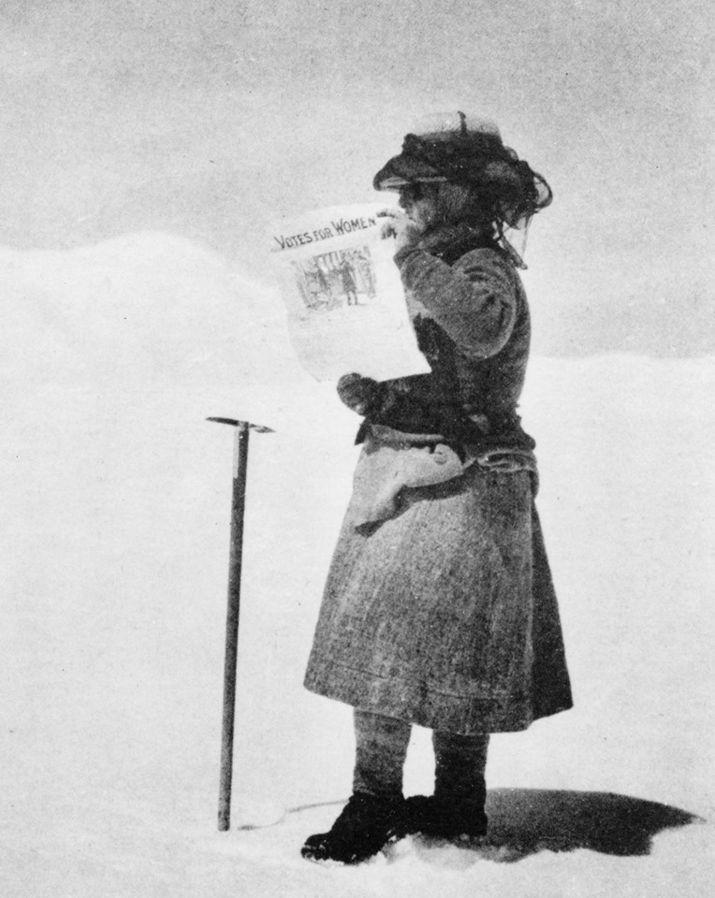 """Photographie en noir et blanc de Fanny Bullock Workman, lors d'une expédition dans le Karakoran. Elle tient une affiche disant """"votes for women"""""""