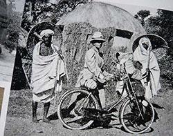 Photographie en noir et blanc de Fanny Bullock Workman, avec sa bicyclette, rencontrant des habitants locaux lors d'un de ses voyages.