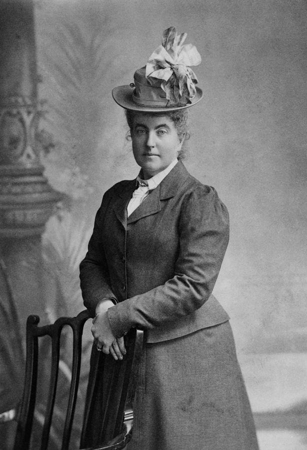 Cette photographie en noir et blanc est un portrait en pied de Fanny Bullock Workman. Debout, les mains sur le dossier d'une chaise, elle porte une jupe et une veste, ainsi qu'un chapeau avec un noeud de ruban.