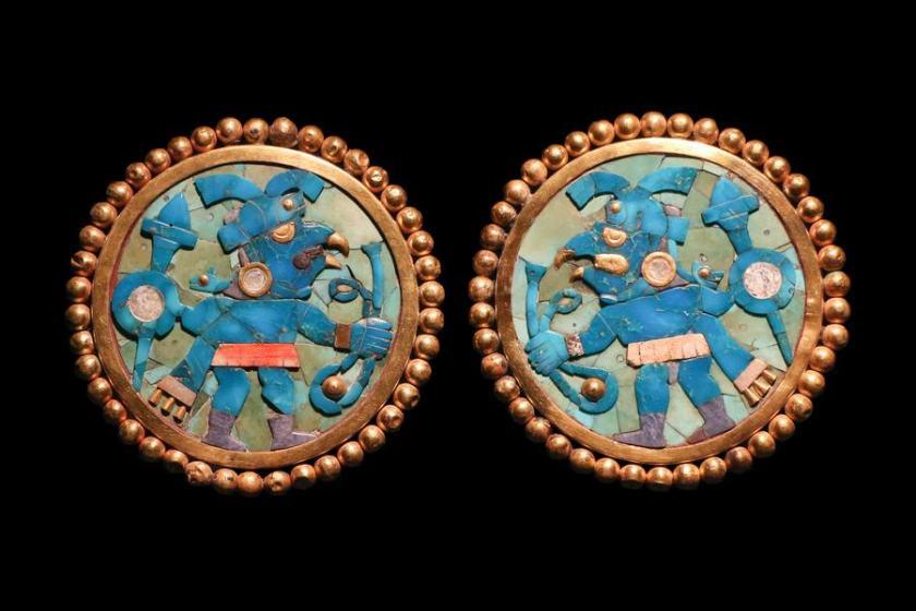 Cette image montre deux boucles d'oreille rondes en lapis-lazuli représentant, sur chacune, un guerrier Moche de profil.