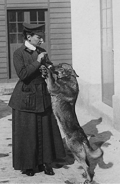 Cette photographie en noir et blanc montre Nicole Girard-Mangin avec sa chienne Dun (pour Verdun). Nicole est débout, en jupe et veste sombre avec une casquette et joue avec sa chienne, debout sur ses pattes arrières.