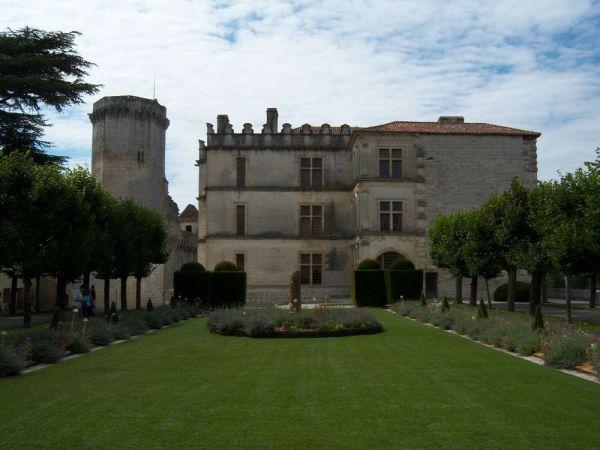 Cette photographie montre le palais Renaissance de Bourdeilles. Au premier rang, les jardins du palais avec une vaste pelouse bordées de rangées d'arbres. Derrière le jardin, le palais en lui-même avec une tour ronde à gauche. Le ciel est voilé de nuages effilochés.