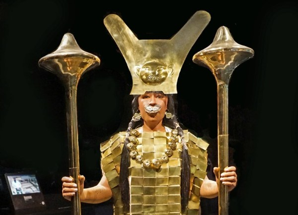 Cette photographie montre une reconstitution en taille réelle de la Dame de Cao. Elle est représentée debout, vêtue d'un riche habit d'or, et porte les objets retrouvés dans sa tombe : deux sceptres en forme de masse, une couronne et un diadème, des bijoux dont un lourd collier. Elle est chaussée de sandales.