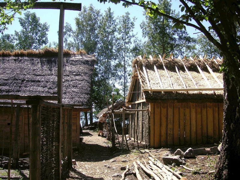 Cette image montre une reconstitution d'habitations en bois dans le site archéologique de Birka.