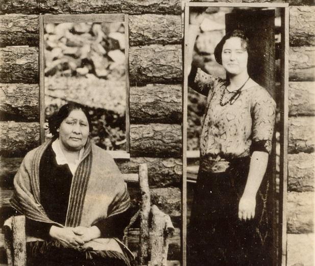 Cette photographie montre Rita Smith et Nettie Brookshire. Les deux femmes se tiennent devant une maison aux murs de bois, l'une est assise et l'autre debout.