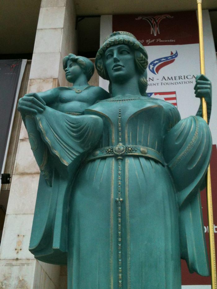 Cette image montre une statue de la reine Teuta, avec un enfant à ses côtés (son beau-fils).