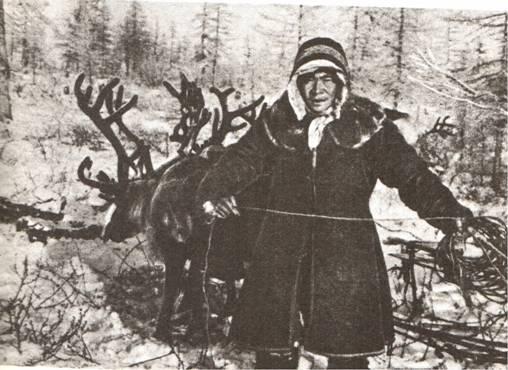 Cette photographie en noir et blanc montre un homme dolgane vêtu d'un manteau épais. Il se tient devant un renne, dans une forêt enneigée.