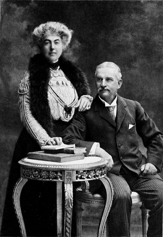 Cette photographie en noir et blanc montre William Workman et Fanny Bullock Workman. William est assis, accoudé à un guéridon sur lequel sont posés plusieurs ouvrages. Fanny est debout à coté de lui, une main posée sur l'épaule de son mari.