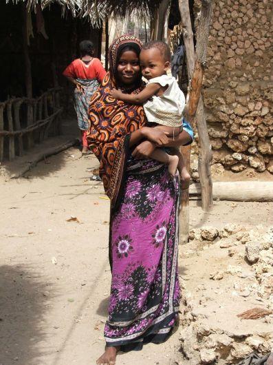 Cette photographie montre une Jeune femme portant le kanga traditionnel à Siyu sur l'Ile Pate. Elle tient un enfant dans ses bras.