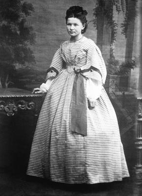 Cette photographie en noir et blanc montre Bertha Benz à l'âge de 18 ans. Elle porte une longue robe à petits carreaux, à la jupe et aux manches évasées. Ses cheveux sombres sont soigneusement coiffés en arrière.